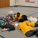 Children laying in a circle, paying attention as a woman points to some papers.