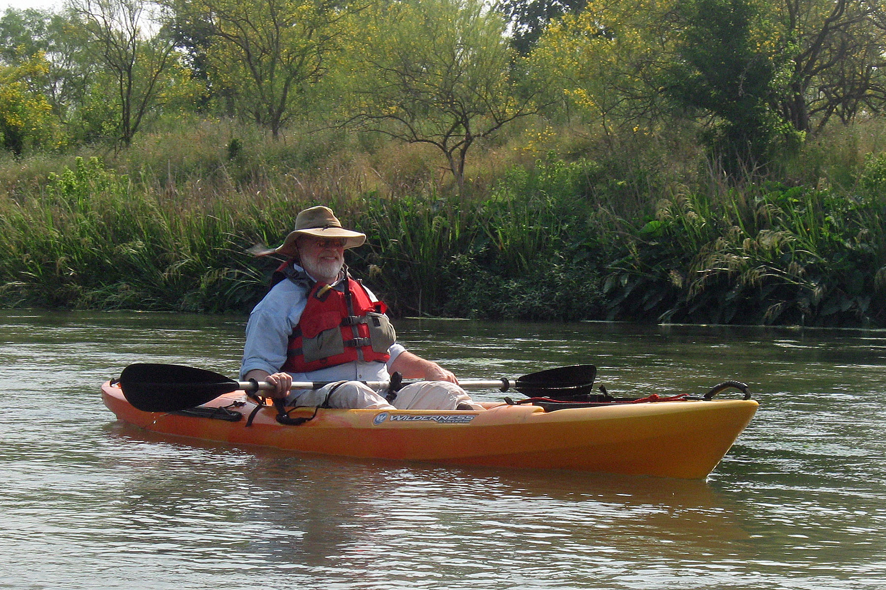 Photo of a man with a wide-brimmed hat and beard in a kayak.