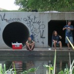 Photo of people fishing on the river in front of a square and circular culvert.