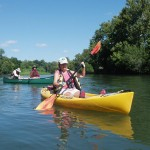 Action shot of a woman paddling a kayak, with people in a canoe behind.
