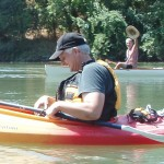 Photo of a man in a kayak looking down, with a kayaker in the background him holding up a hat in greeting.