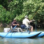Photo of two men fishing from a small pontoon boat.