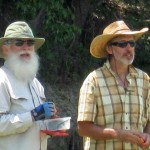 Medium shot of two men with wide-brimmed hats and sunglasses eating baby carrots.