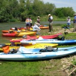 Photo of a line of colorful kayaks on a riverbank.