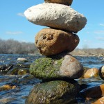 Photo of five different colored rocks stacked atop one another in the river.