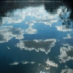 Photo of blue sky and fluffy white clouds reflected from the surface of the river.